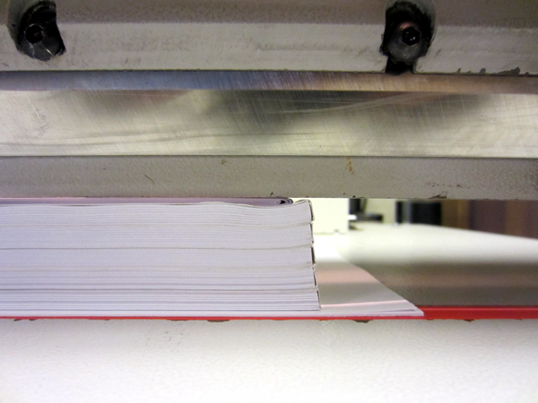 Folded sheets creating gap between cutter clamp and book spines.